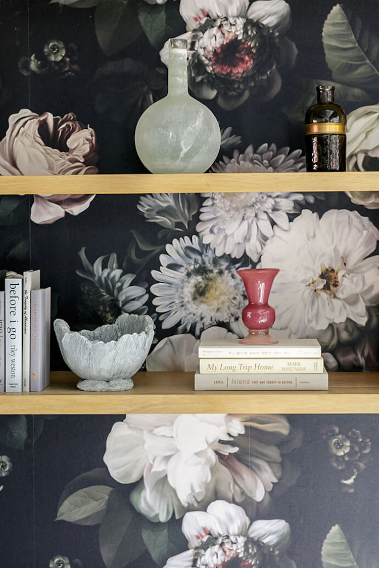 Black floral wallpaper behind wood shelves