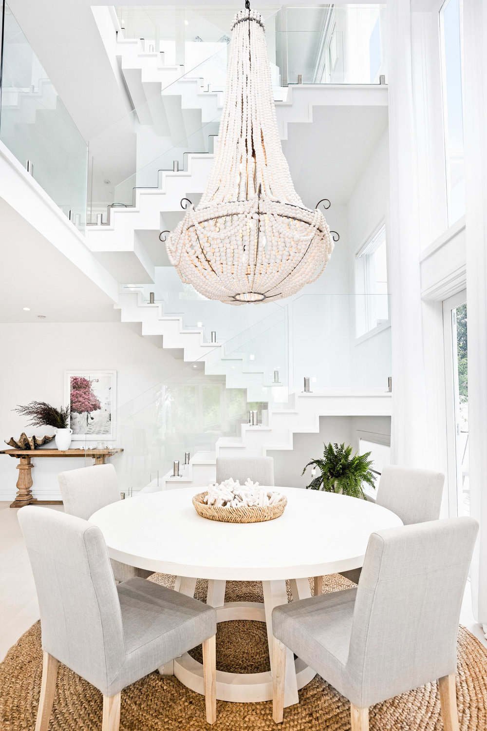 Dining room with grey chairs and white beaded chandelier