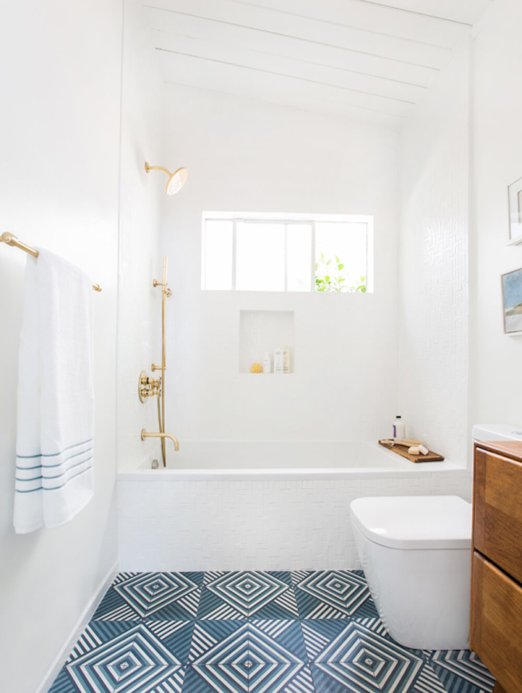 Emily Henderson's guest bathroom with gold fixtures and blue tile floor