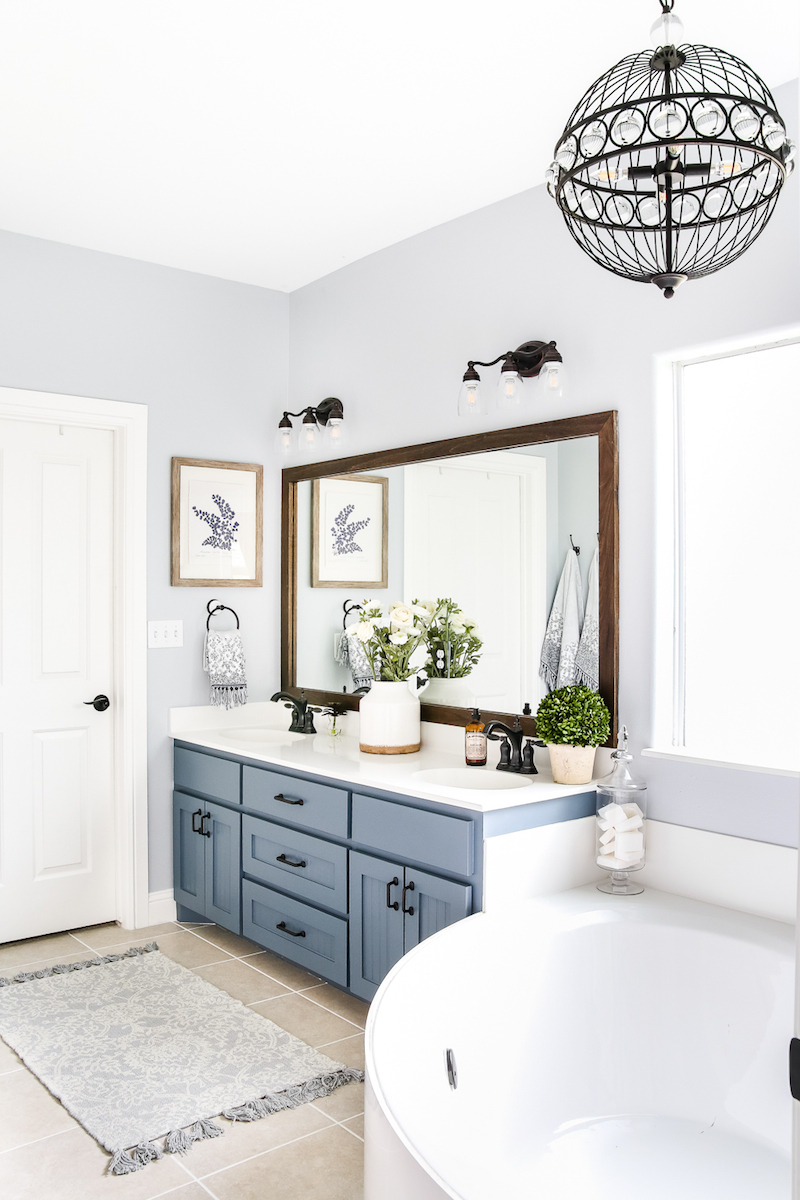 Faded blue bathroom vanity and corner tub via maison de pax