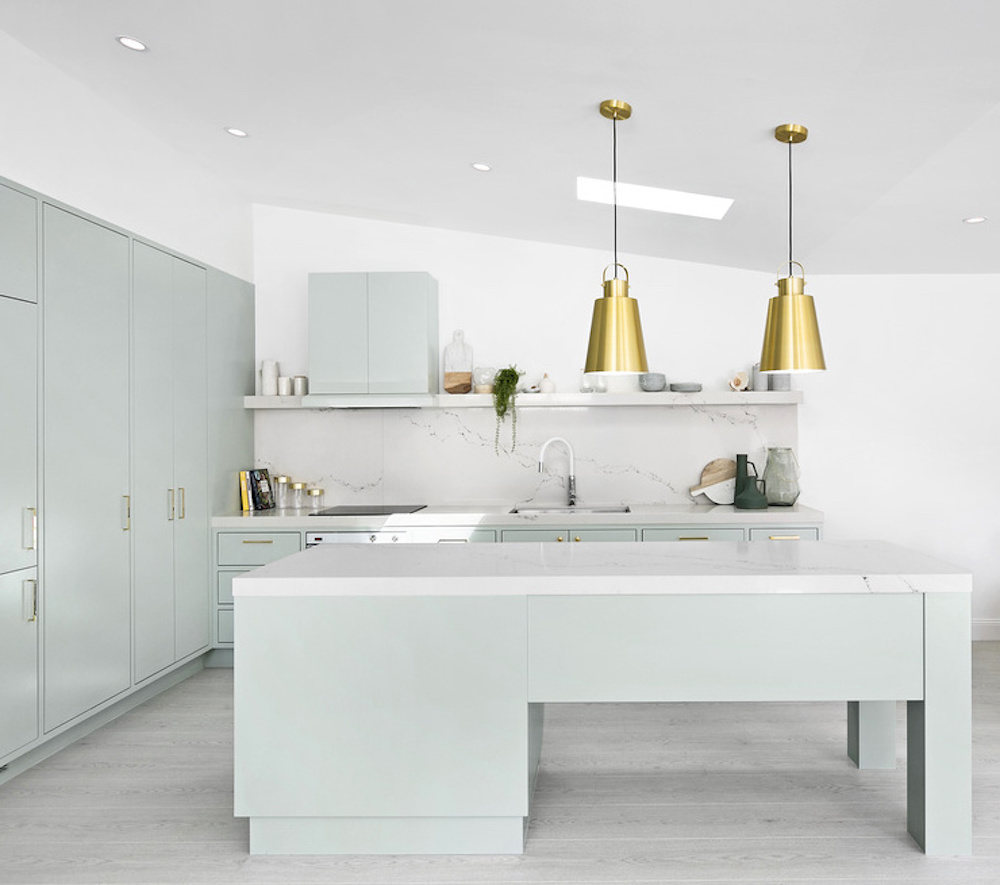 Kitchen with mint green cabinets and gold pendant lighting