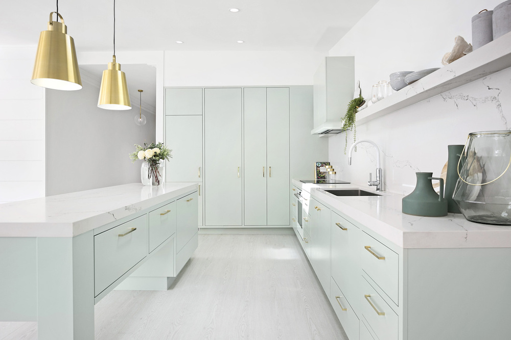 Kitchen with mint green island cabinets and two gold pendants