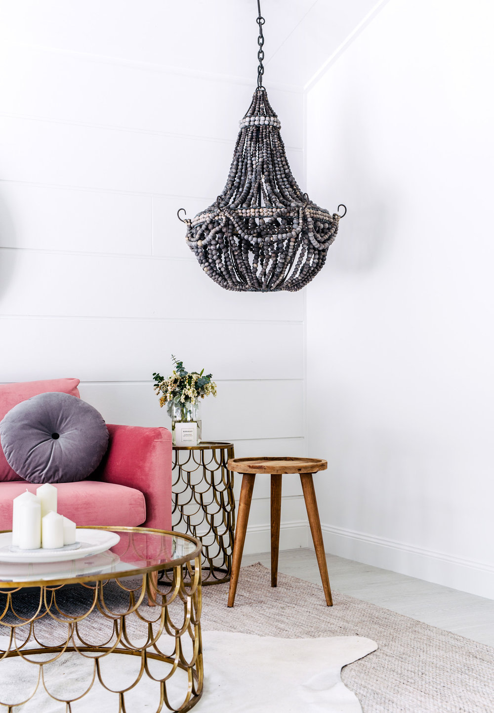 Living room by Three Birds Renovations with pink couch and black beaded chandelier