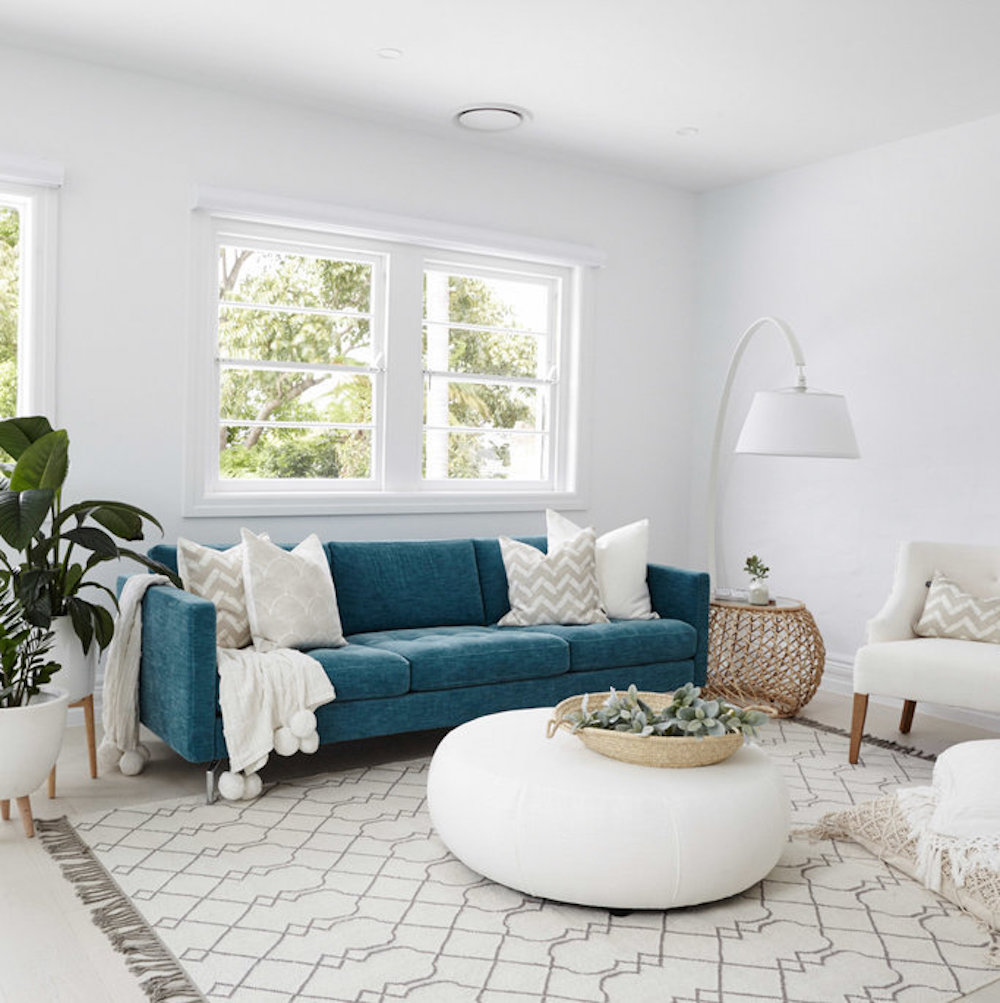 Living room with dark teal couch and neutral pillows