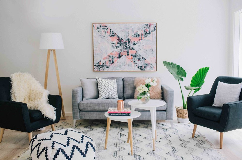 Living room with gray couch and 2 side tables as coffee tables. Design by Three Birds Renovations