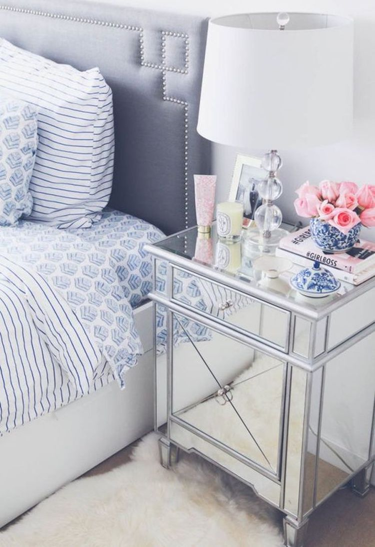 Mirrored nightstand with table lamp, girlboss book, and candle