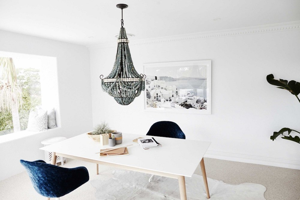 Office with beaded chandelier and blue velvet chairs