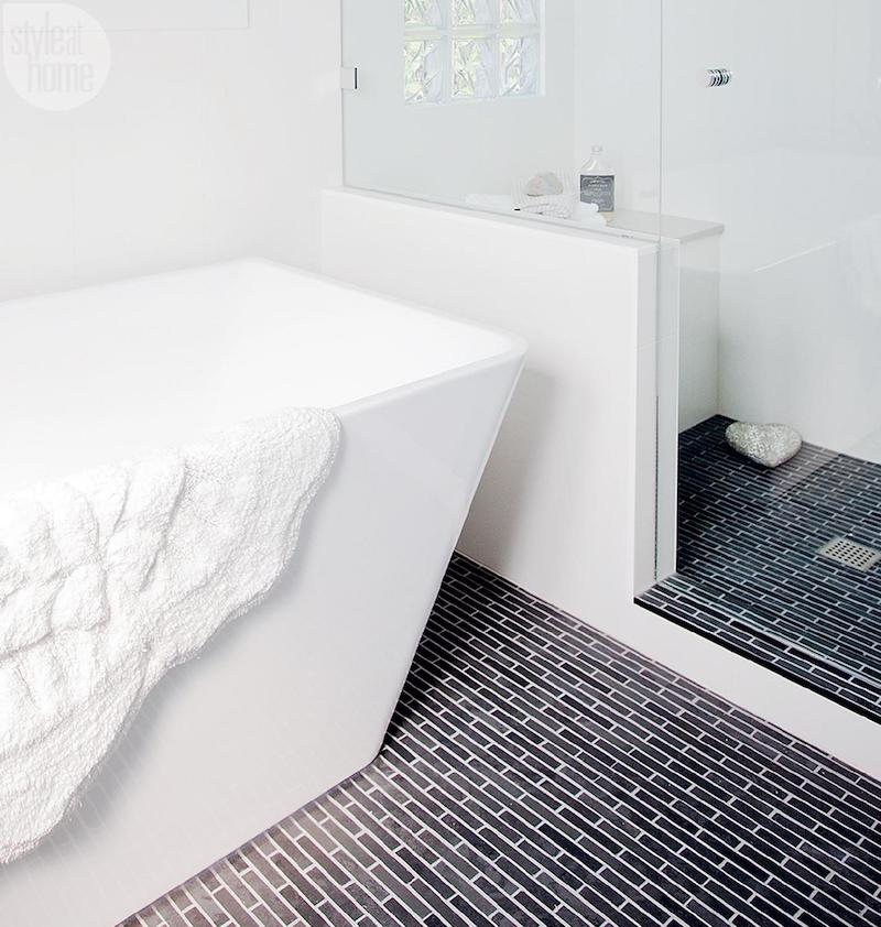 Rectangular tub in bathroom with black floor tiles