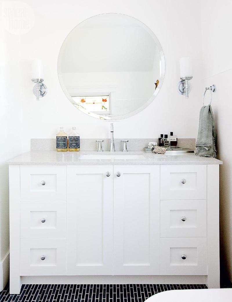 White bathroom vanity with circle mirror