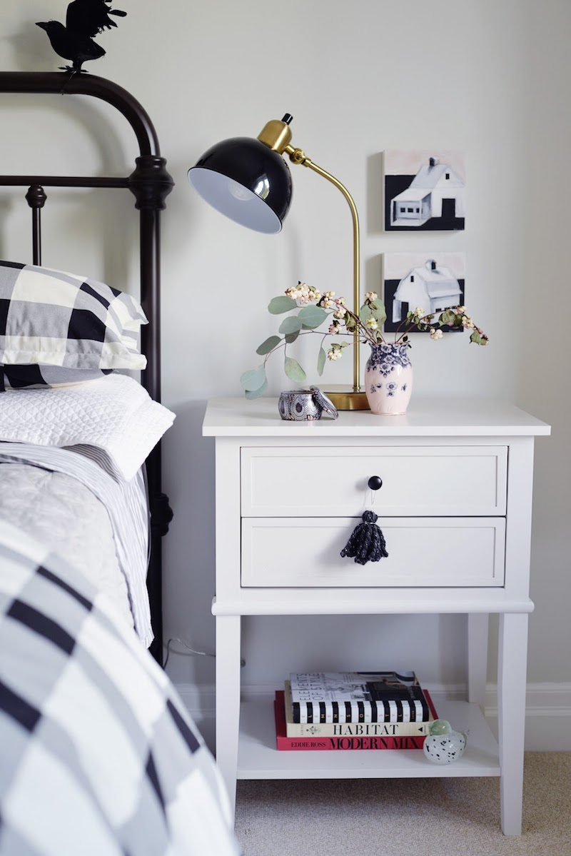 White bedside table with black task lamp in fall bedroom