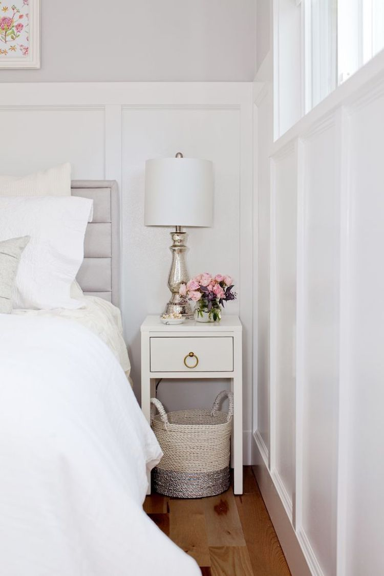 White bedside table with silver lamp and pink flowers