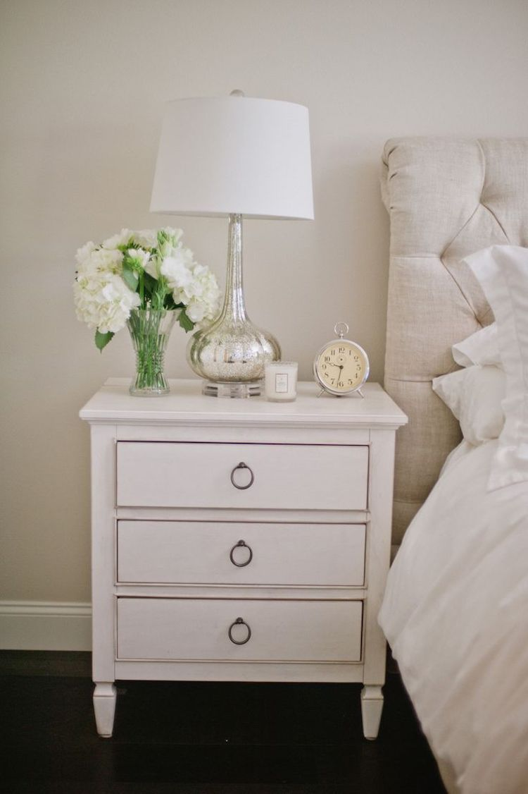 White nightstand with silver table lamp and alarm clock