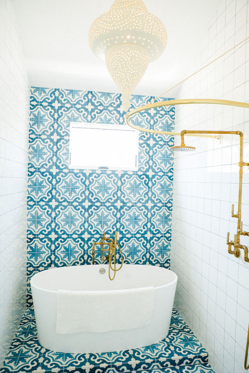 Turquoise Spanish tiling behind white oval tub