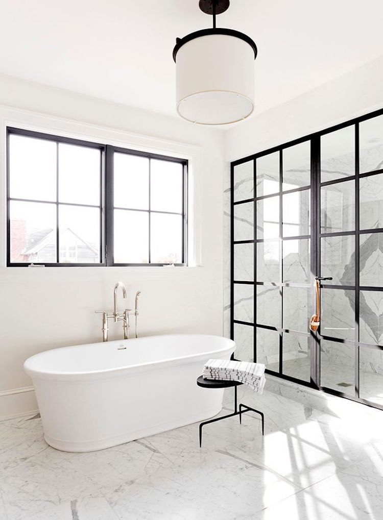 White bathtub in marble floor bathroom with black window panes via Tamara Magel