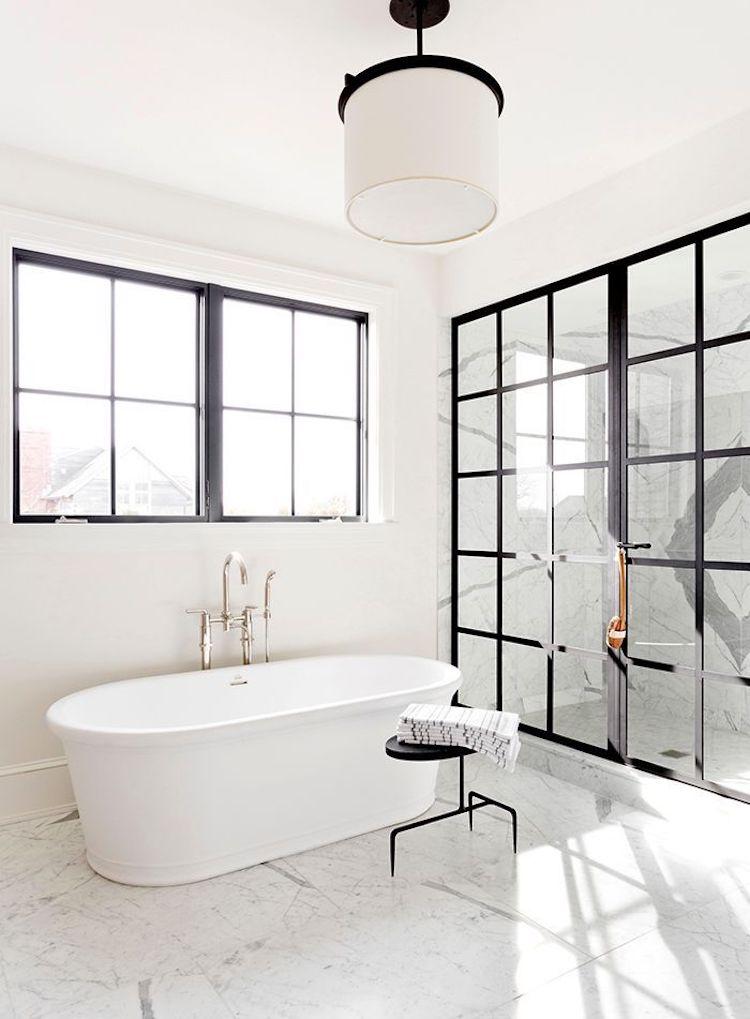 White bathtub in marble floor bathroom with black window panes via Tamara Magel