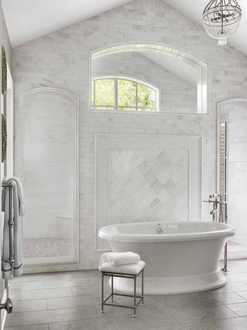 White tub in bathroom with shower and crystal chandelier via Mitchell Wall