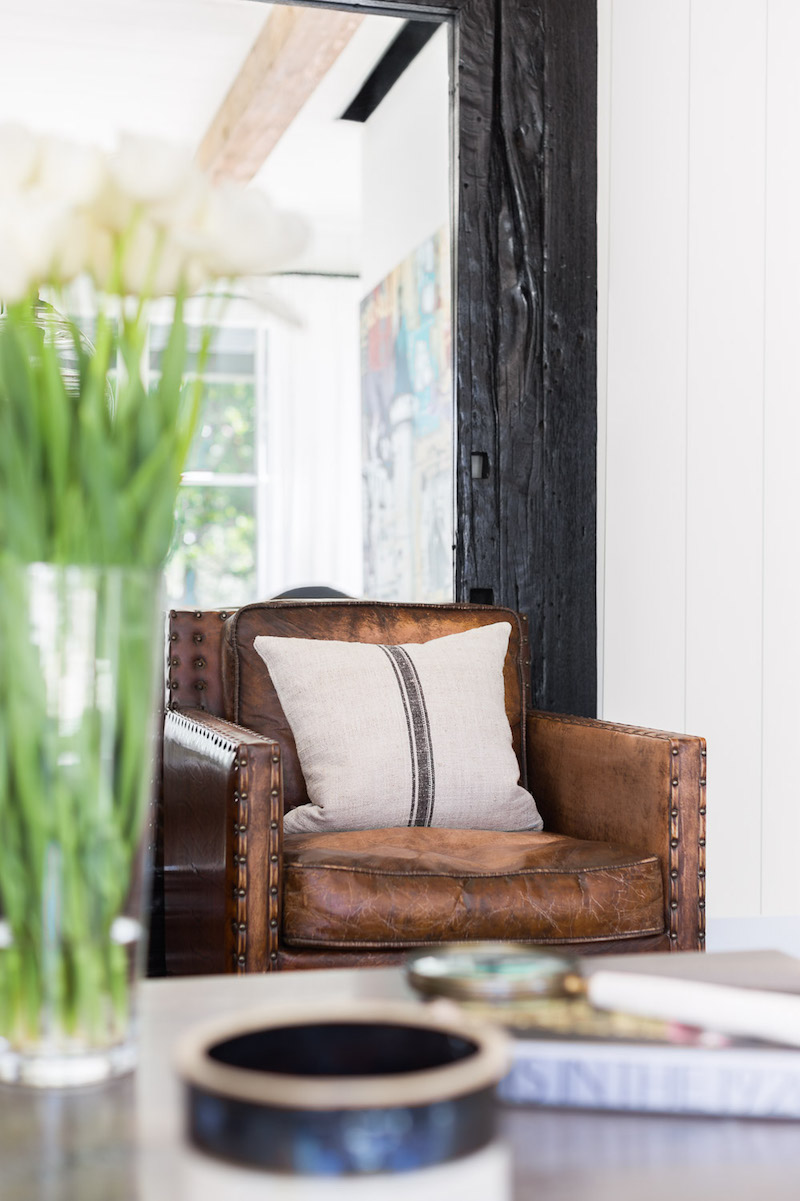 Brown leather chair with Farmhouse throw pillow in the living room