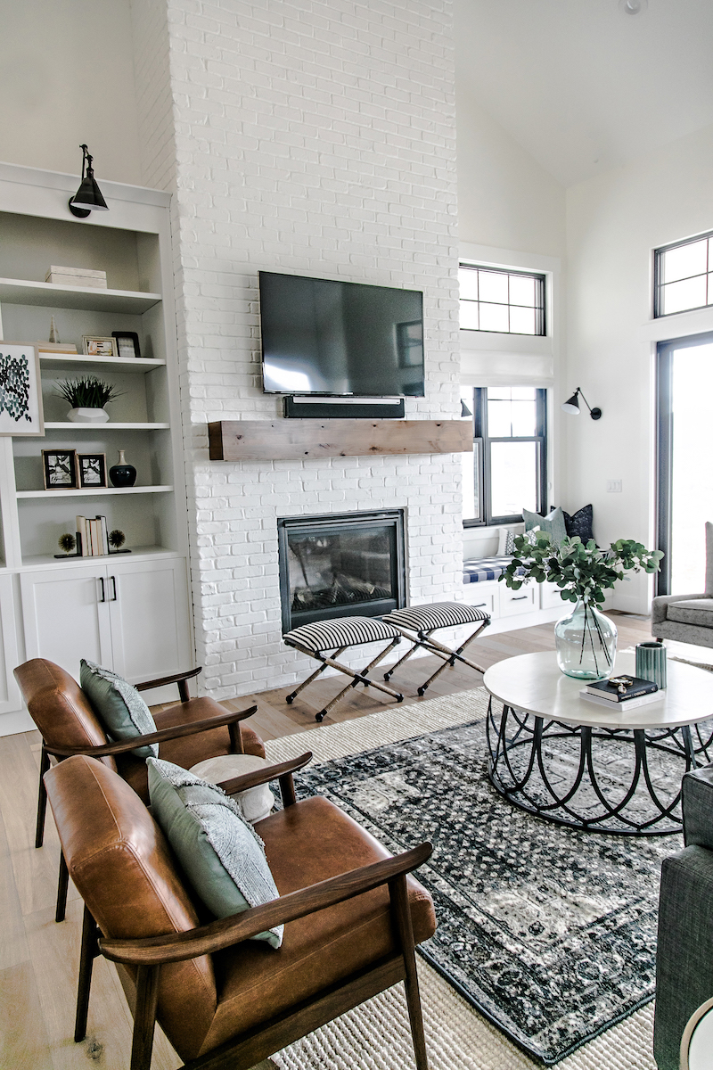 Two matching brown mid-century leather chairs in Farmhouse living room