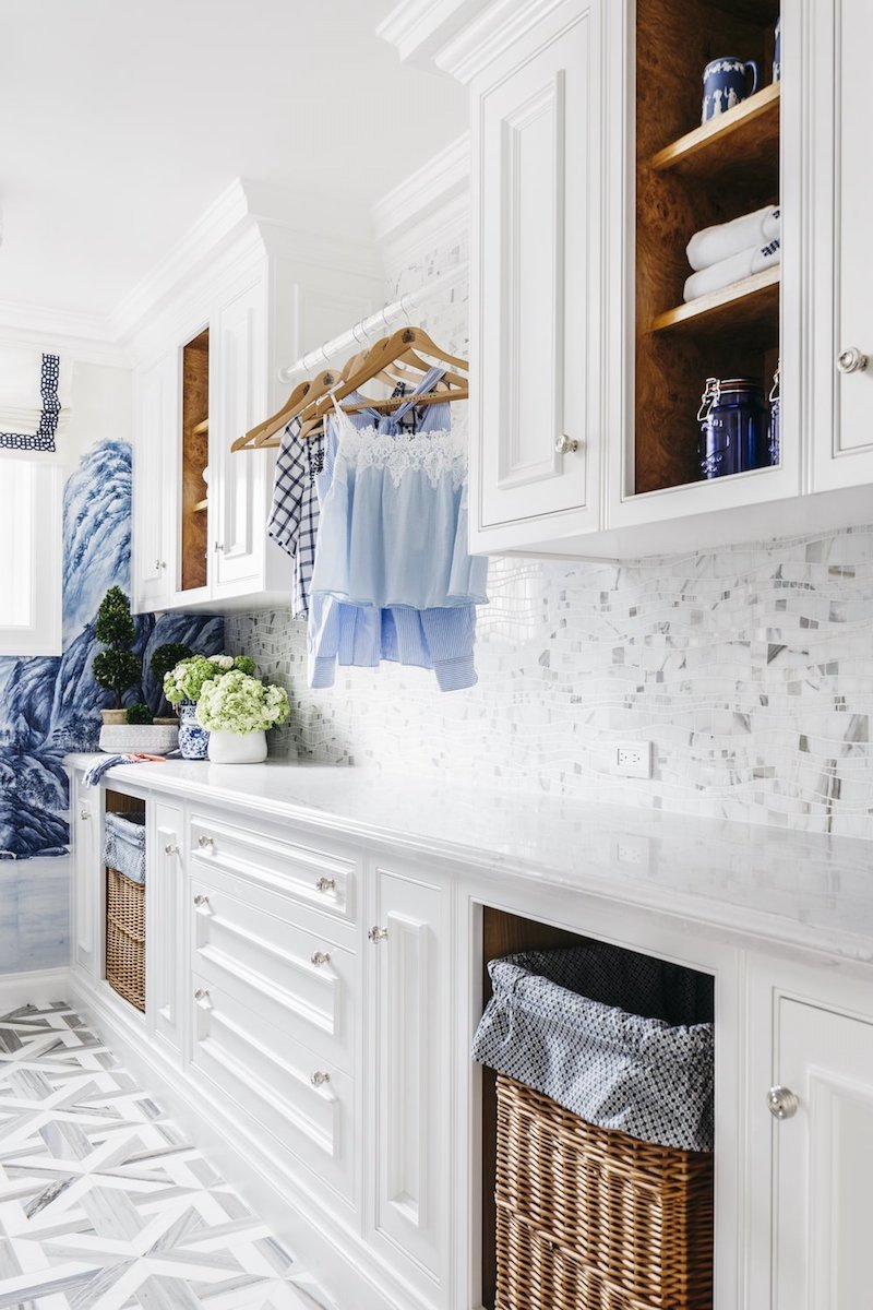 Clothes hanging station in white laundry room with parquet marble floors
