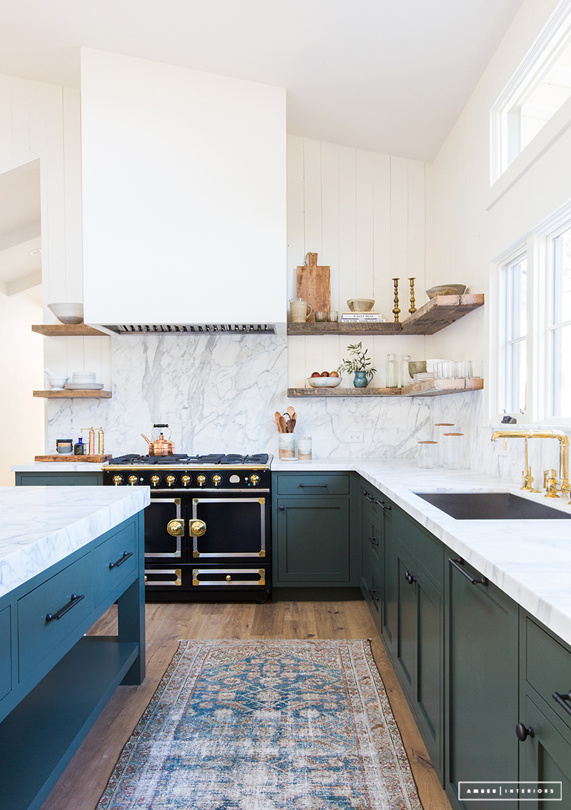 Dark green cabinets with marble backsplash, French Oven, and wood open shelving via Amber Interior Design