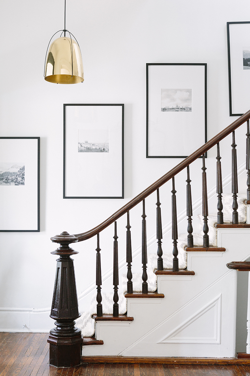 French-Inspired entryway staircase with black frame art