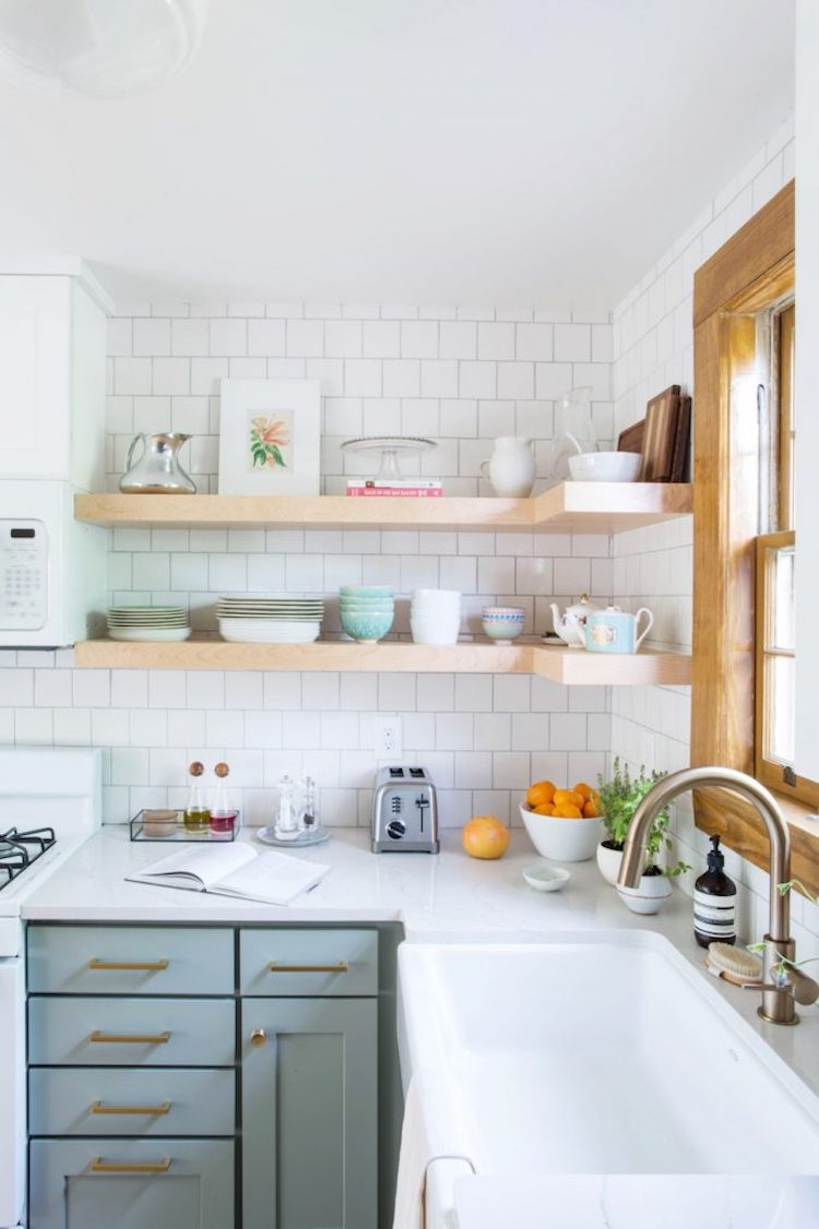 Mint green kitchen cabinets below neutral open shelves kitchen with white backsplash tiling via The Everygirl