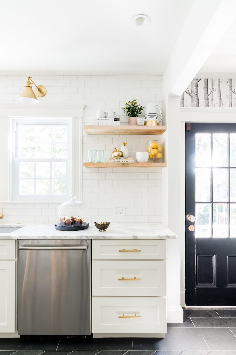 Open shelving kitchen with marble countertops and white subway tiling