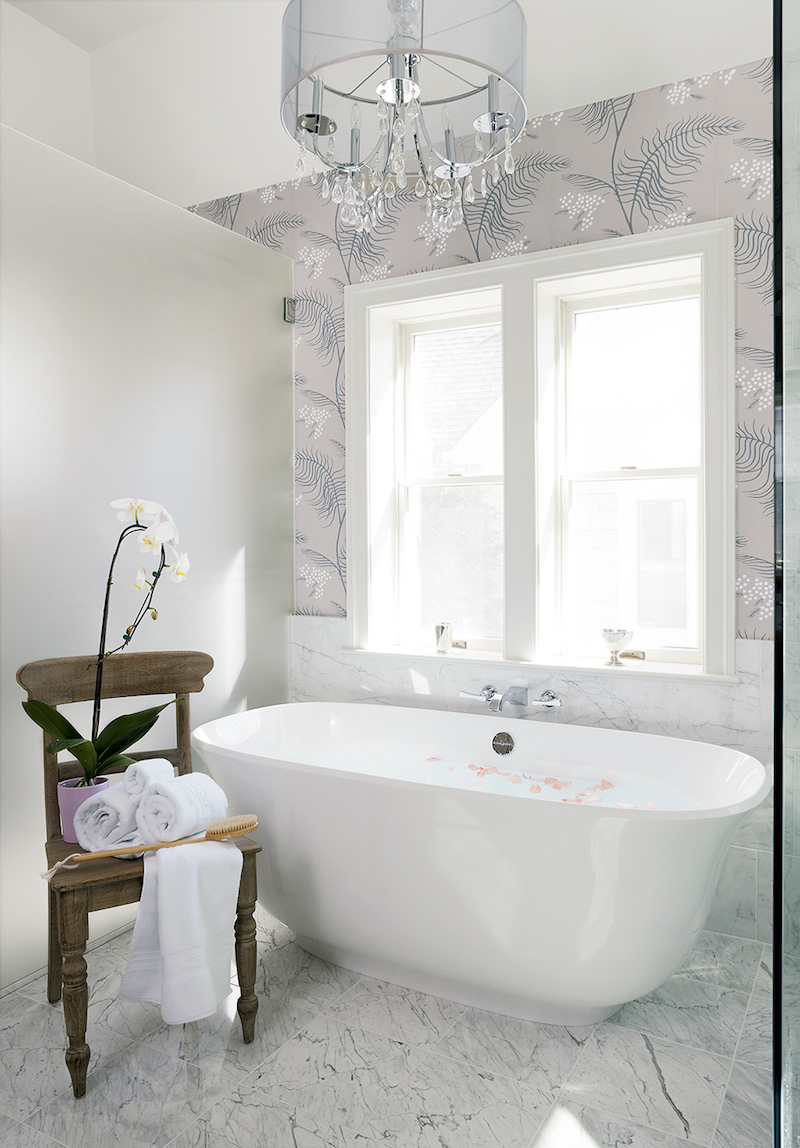White bathtub with lavender floral wallpaper
