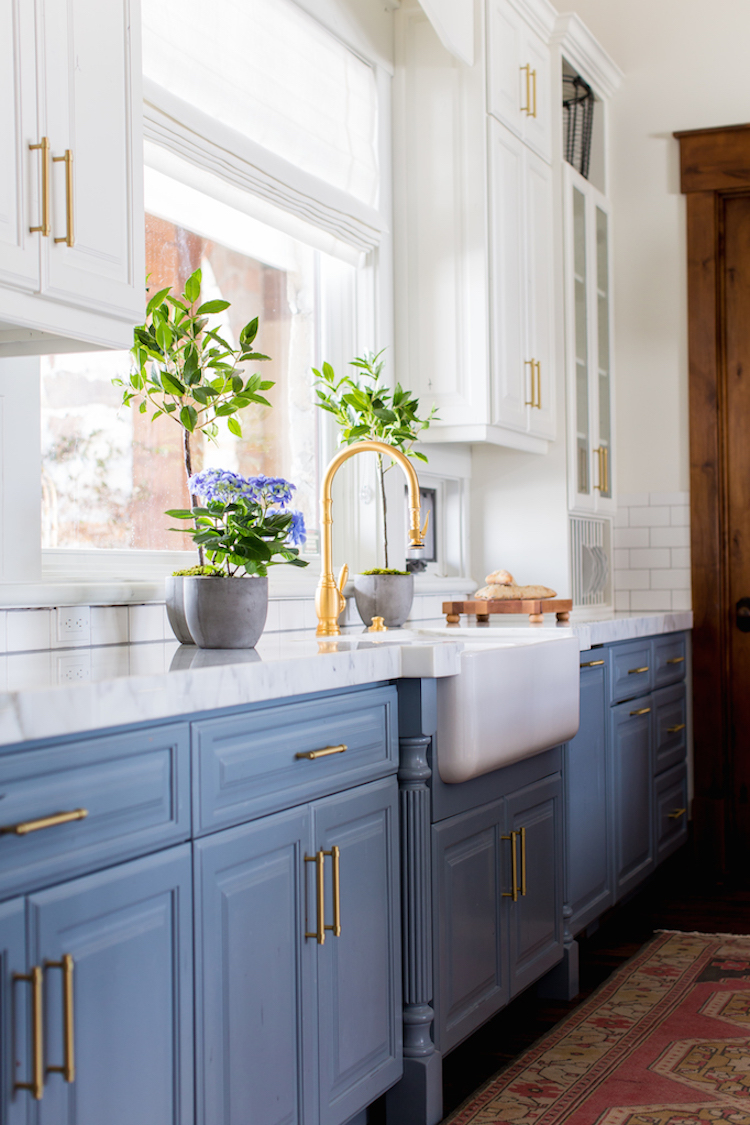 White farmhouse sink with blue kitchen cabinets via Becki Owens