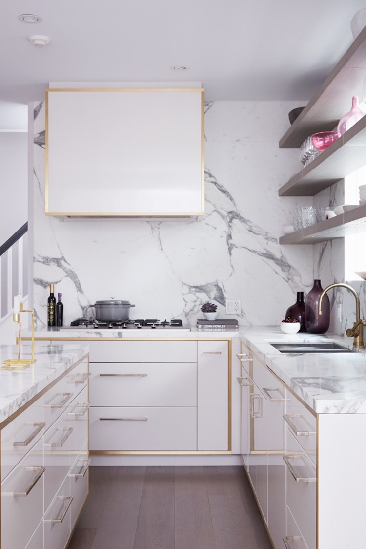 White marble backsplash kitchen with gold hardware via Tara Fingold