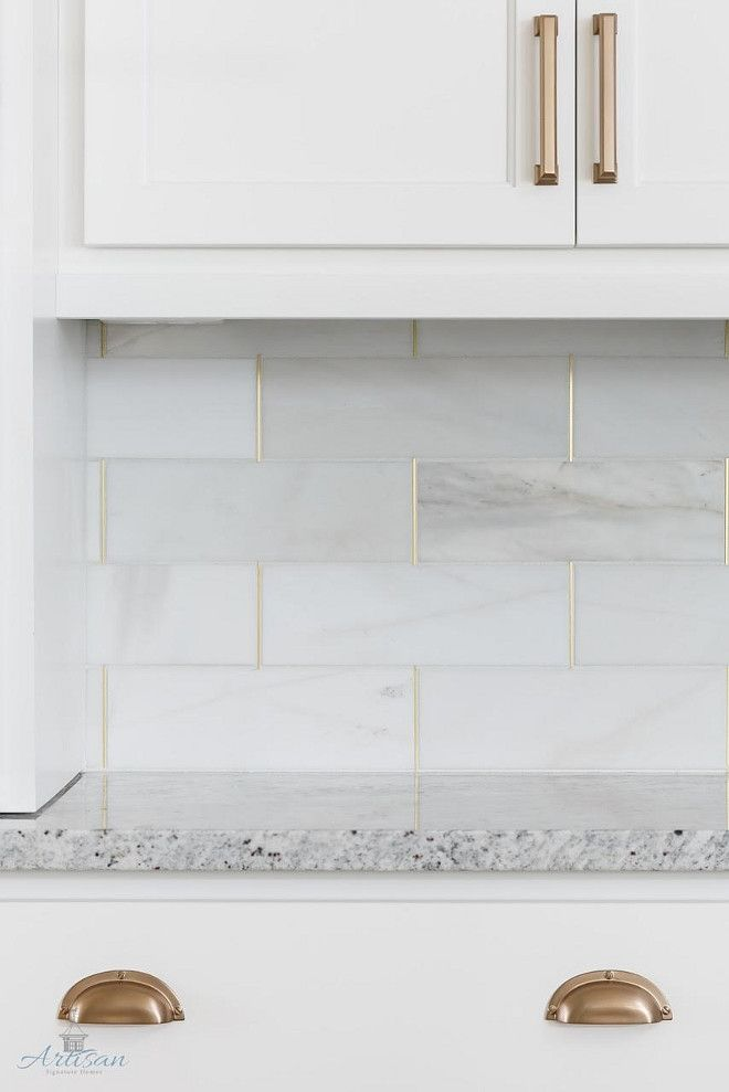 White marble kitchen backsplash with marble tiles brass grout via Artisan Signature Homes