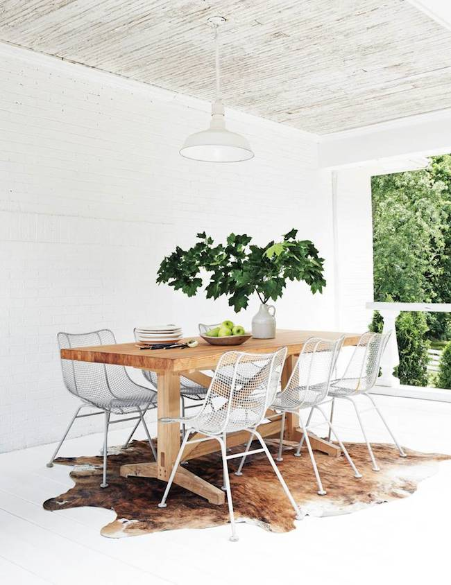 Cowhide rug beneath outdoor dining room
