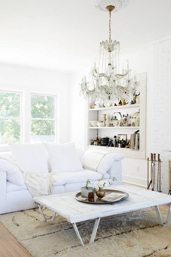 Farmhouse living room with white sofa and crystal chandelier and wooden coffee table