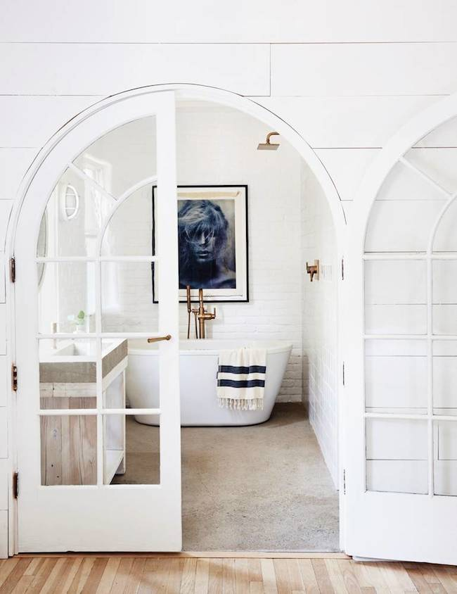 Freestanding bathtub in farmhouse country home with arched doorway