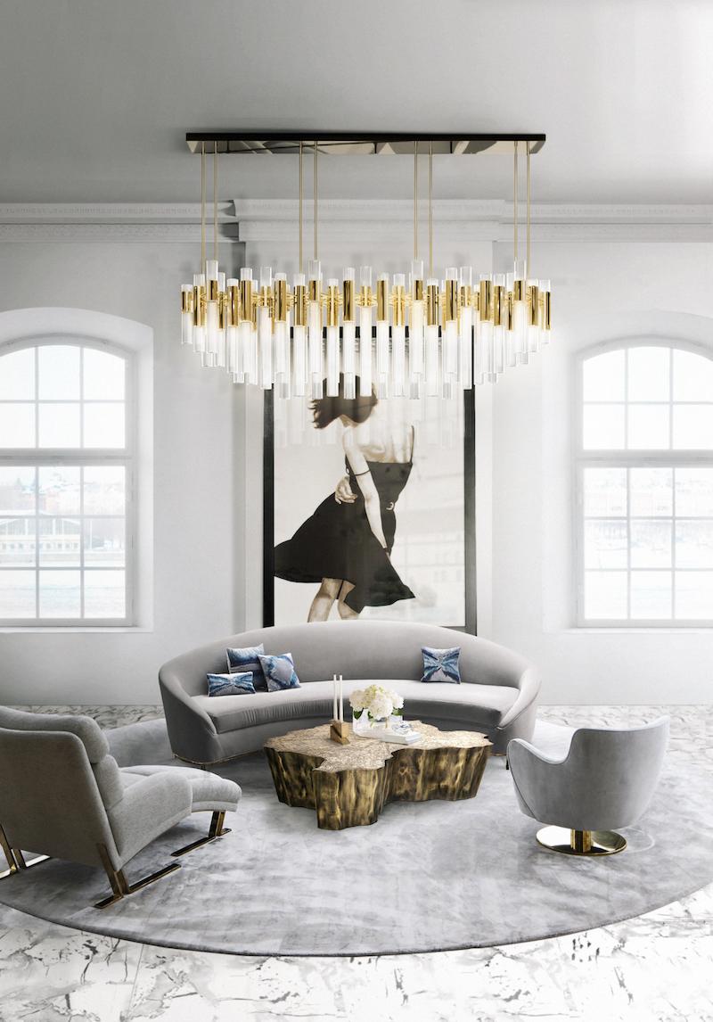 Grey velvet sofa in modern living room with white and gold flute chandelier