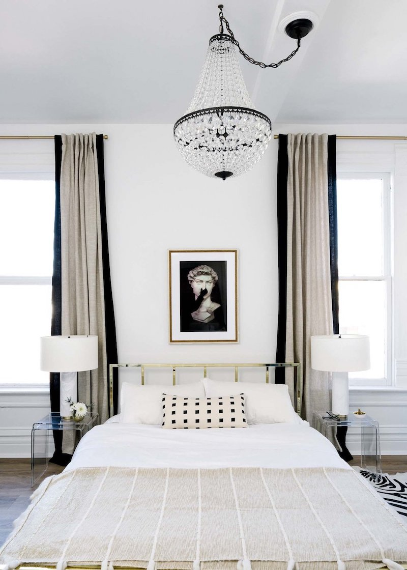 Bedroom with gold headboard, neutral curtains and crystal chandelier via Shelby Girard
