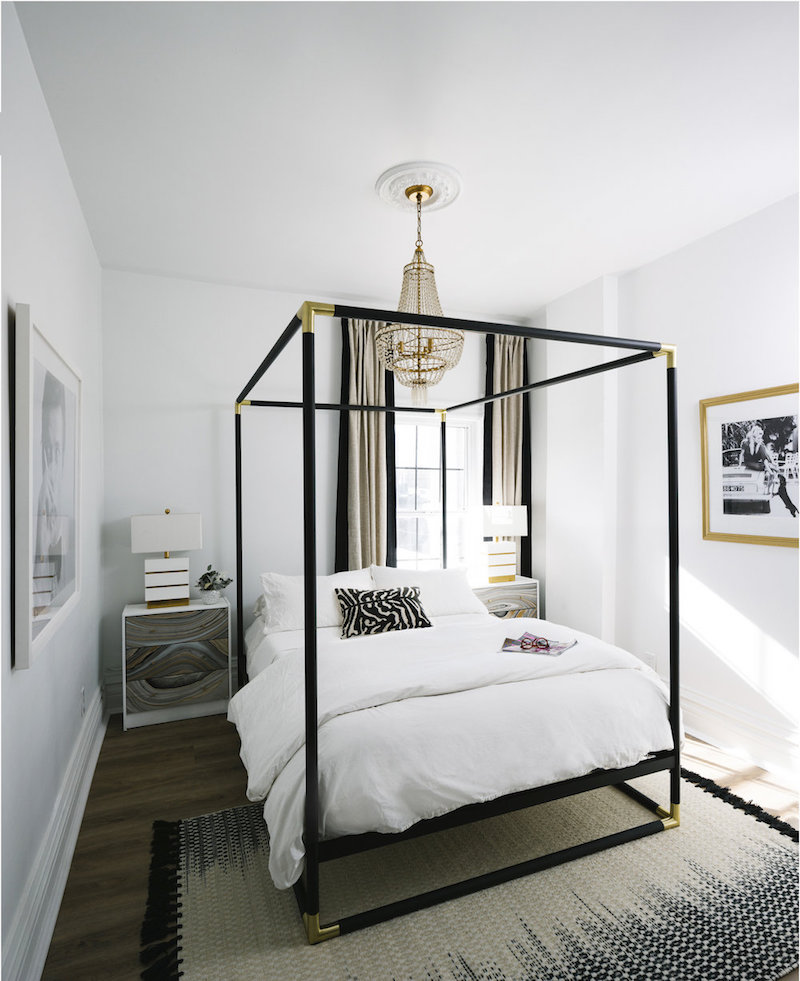 Bedroom with minimal black canopy bed and gold crystal chandelier via Shelby Girard