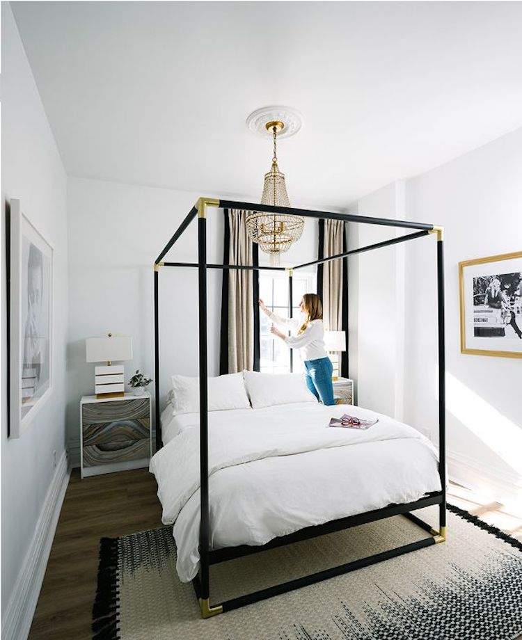 Black Canopy Bed by CB2 with French crystal chandelier via MyDomaine