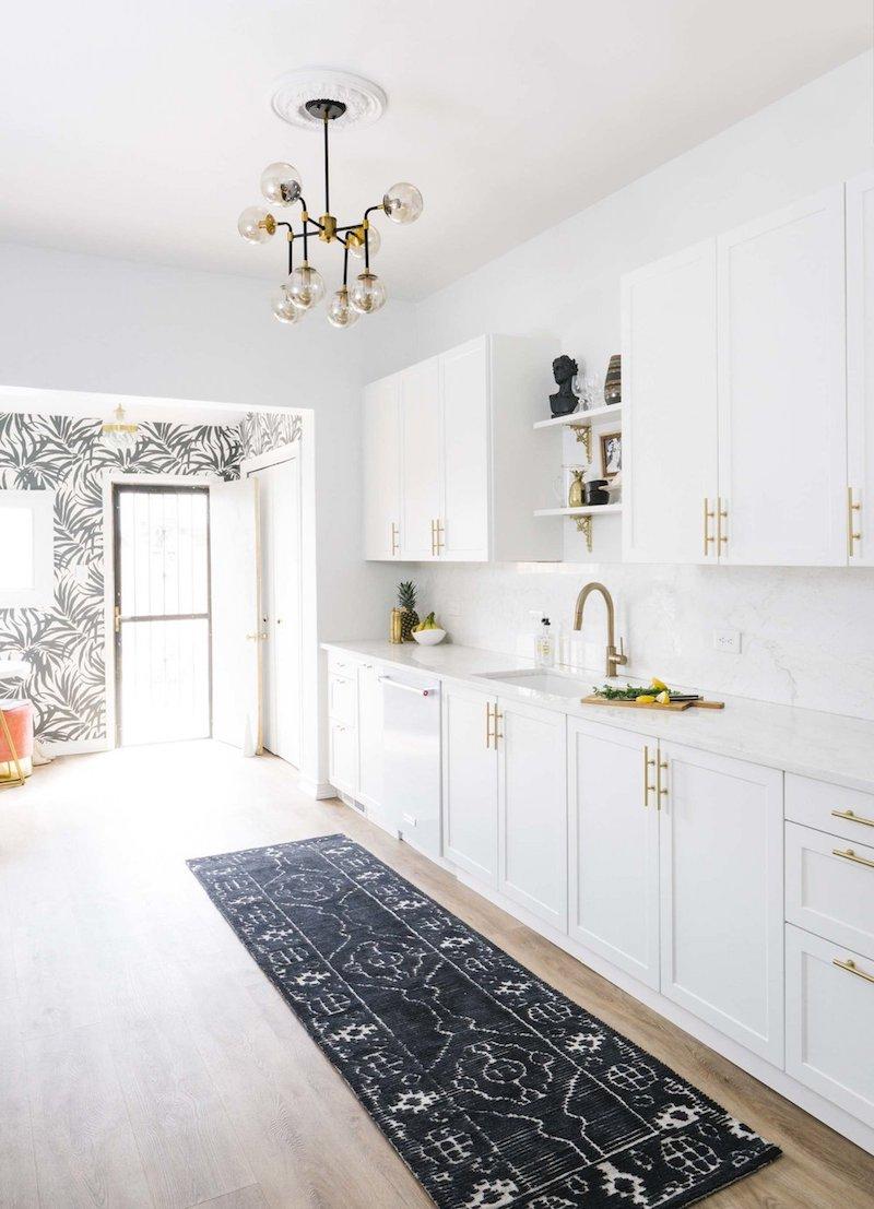 Black runner rug in white kitchen with brass hardware via Shelby Girard