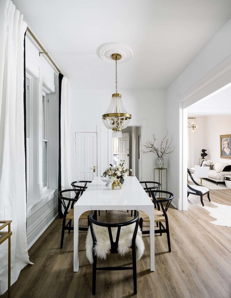 Black wishbone chairs with white dining room table and crystal chandelier via Shelby Girard