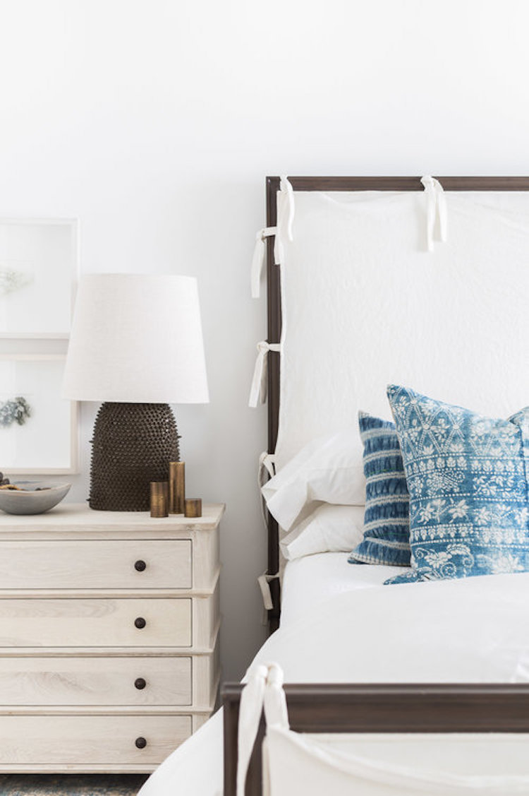 Blue pillows on white bed in bedroom by Nicole Davis