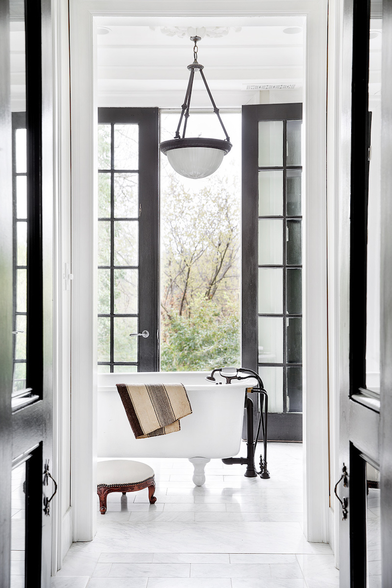 Early 20th century bathroom with floor to ceiling windows and freestanding tub