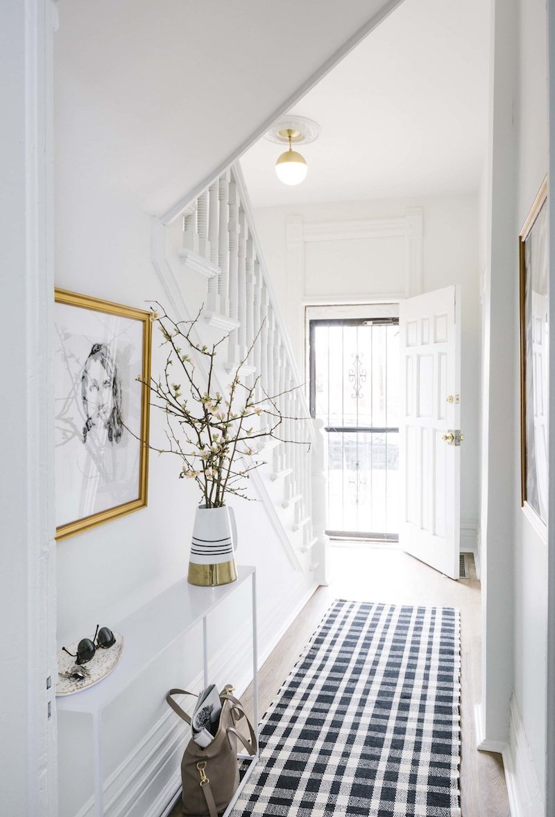 Entrance hallway with black and white rug via Shelby Girard
