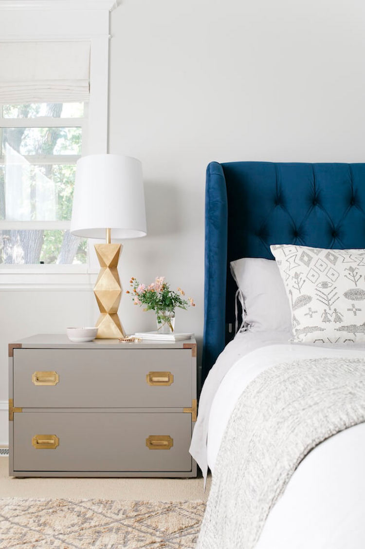 Gold table lamps in bedroom with navy blue tufted headboard