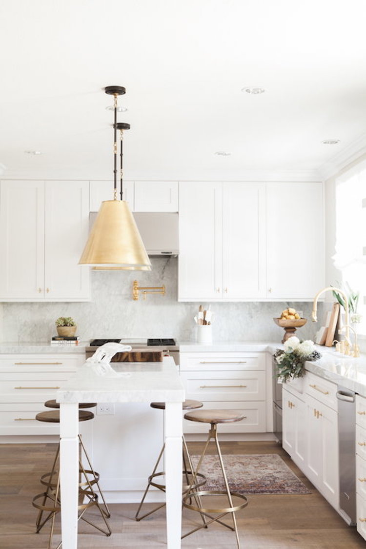 Kitchen with marble backsplash and gold pendant lights by by Nicole Davis