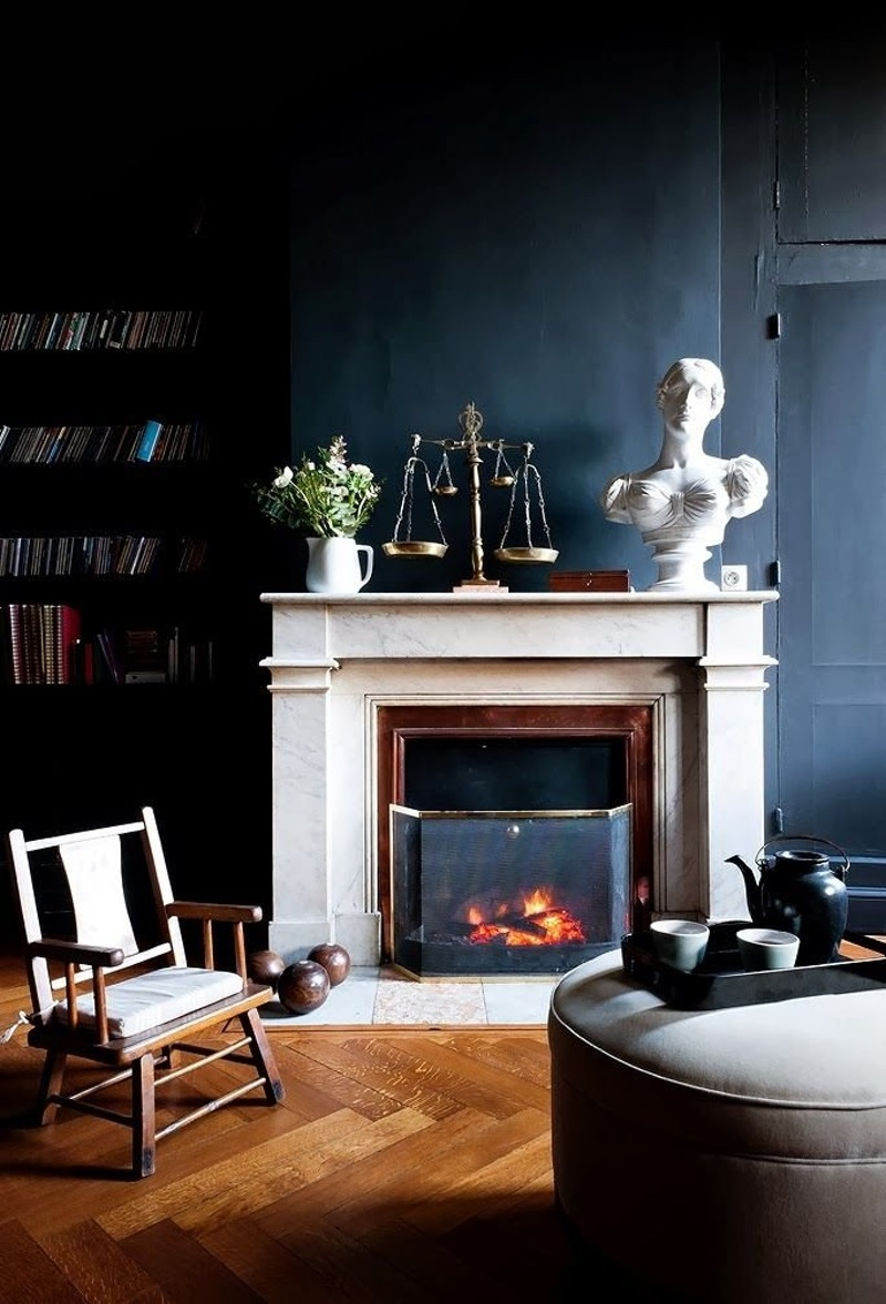 Large white bust on fireplace in dark wall living room via GAP Interiors