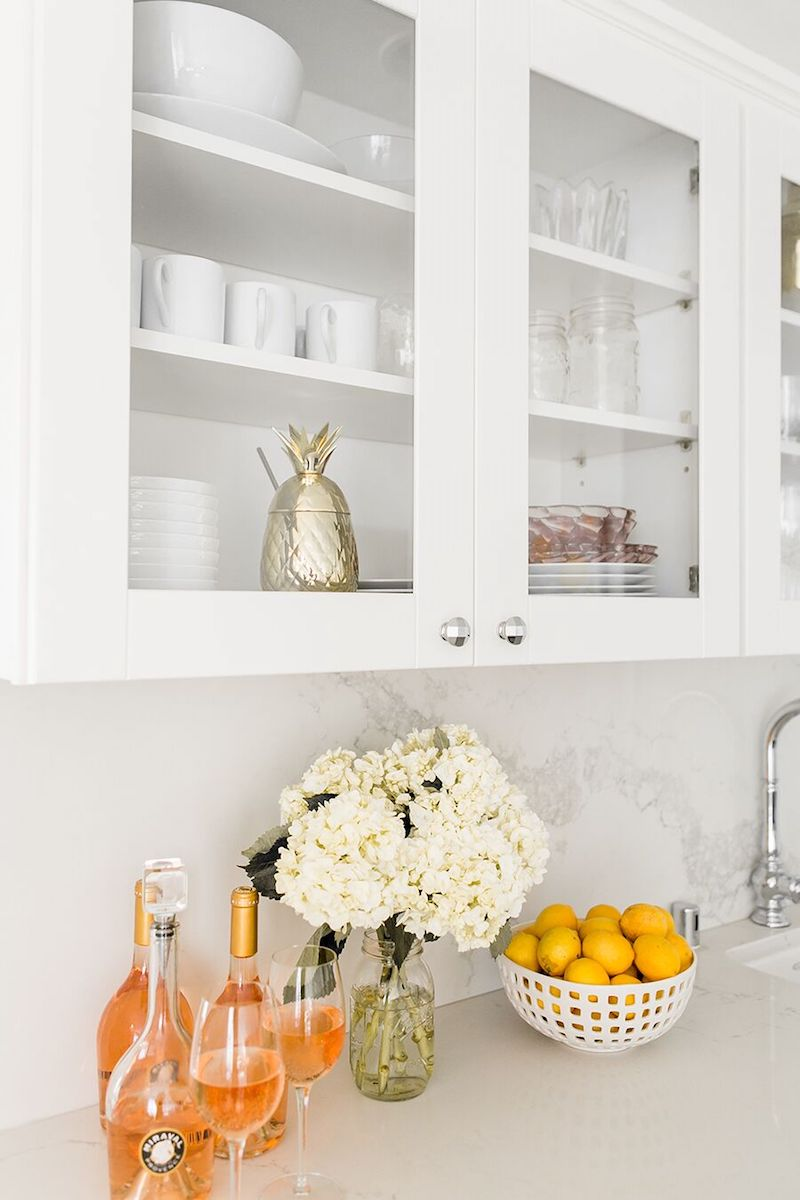 Lemon basket with flowers and wine in kitchen with glass cabinets via Sydne Summer