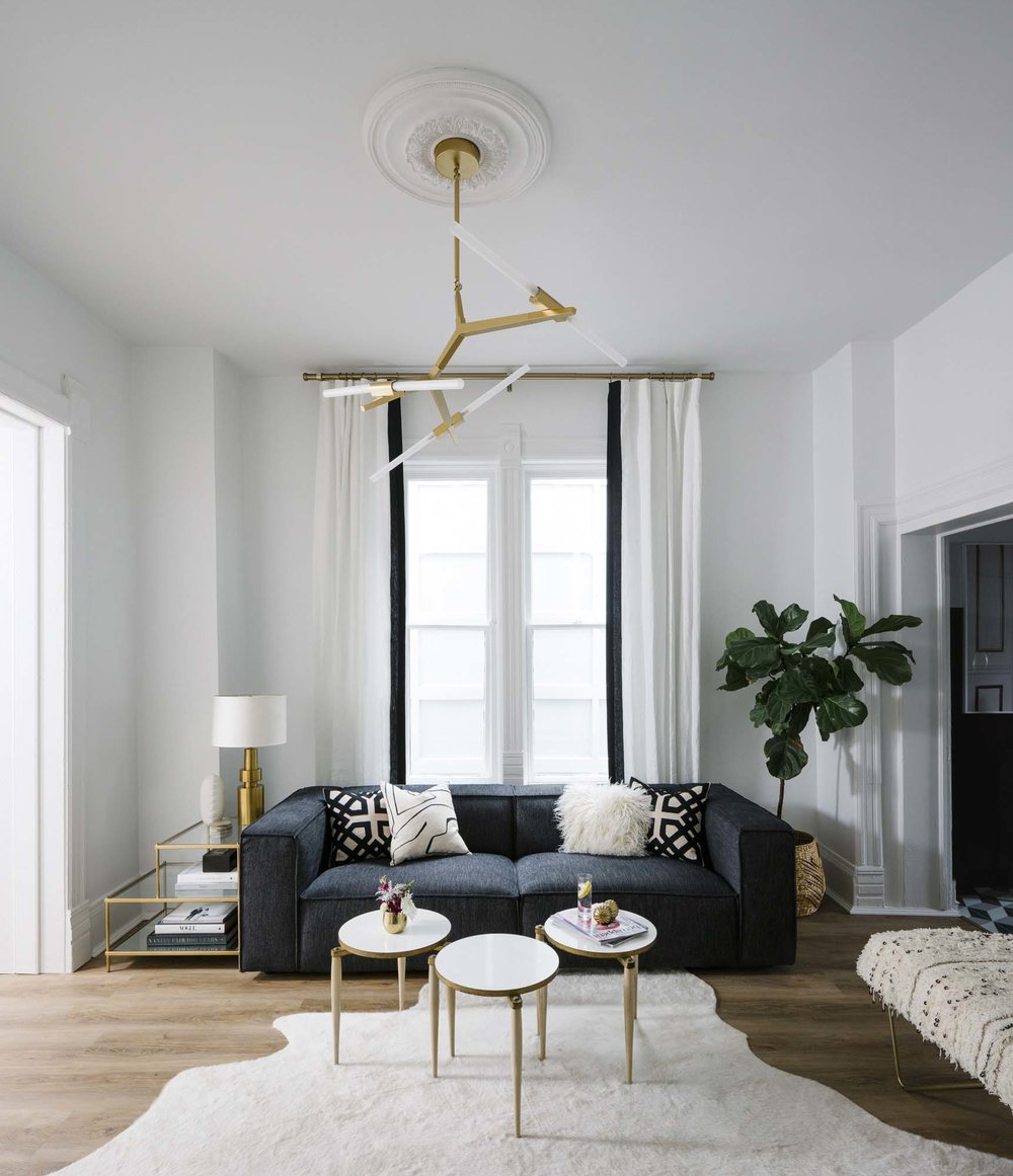 Living room with dark grey sofa and white and gold accents via Shelby Girard