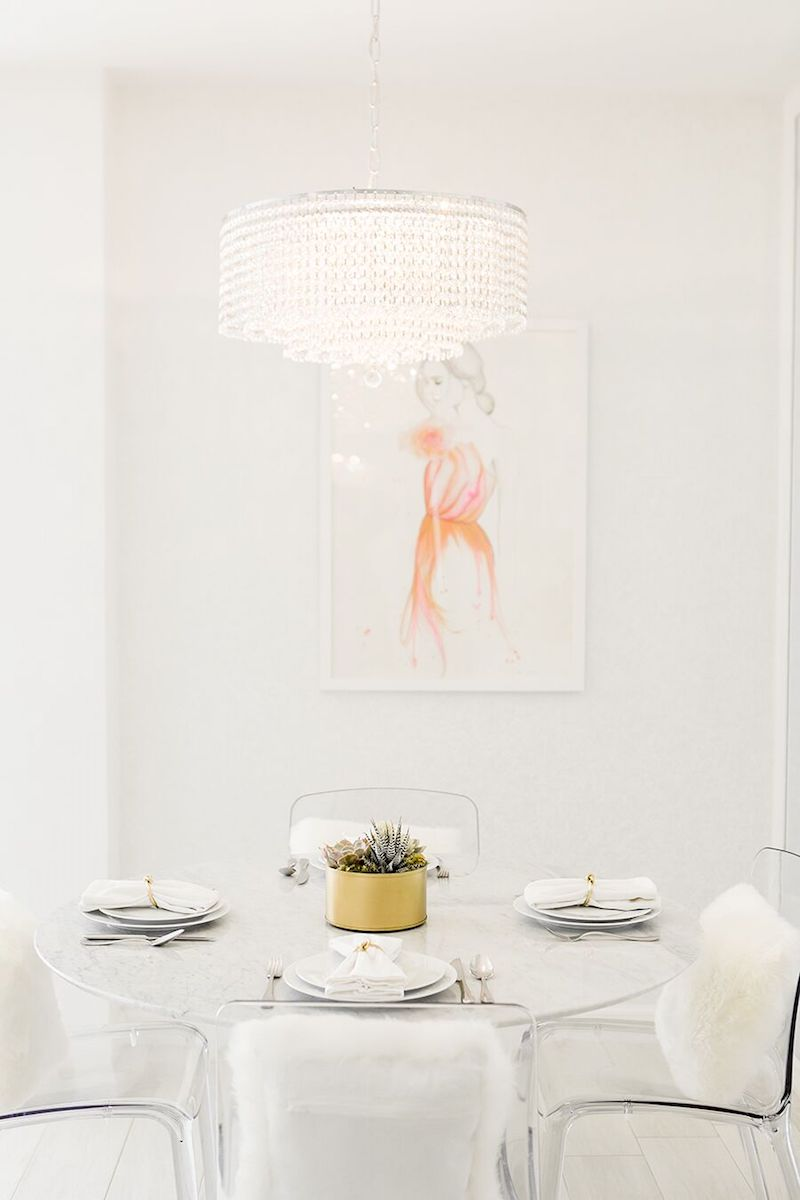 Marble dining table with lucite dining chairs and white fur pillows via Sydne Summer