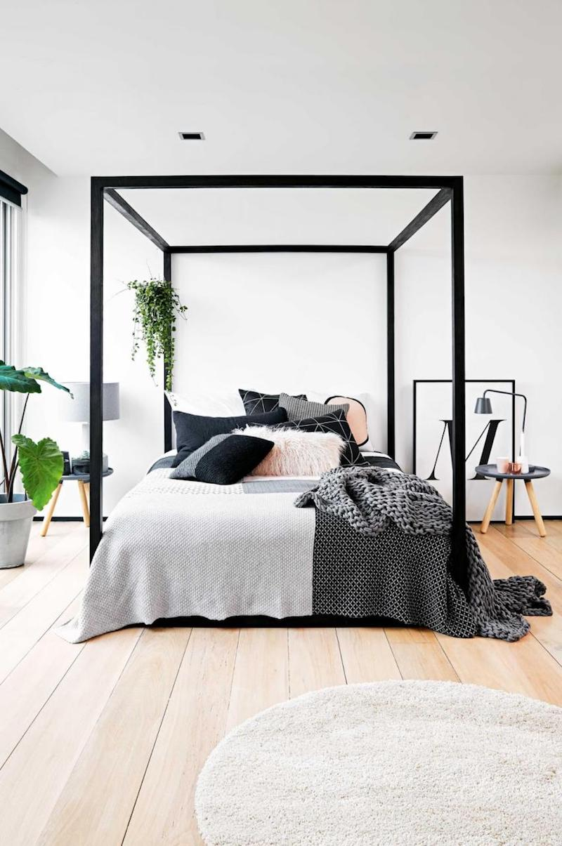 Minimal black canopy bed with grey linens in bedroom via Inside Out Mag